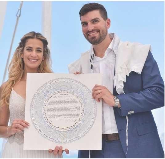 jewish couples holding papercut ketubah